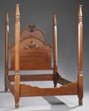 American Late Victorian Carved Walnut Poster Bed, late 19th c., the arched headboard with a pierced grape and leaf crest, over an ap...