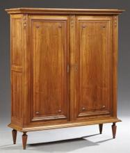 French Louis XVI Style Carved Walnut Armoire, 19th c., the stepped crown over two raised panel cupboard doors within carved stiles,...