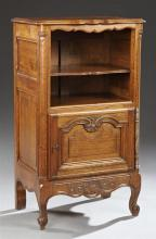 French Louis XV Style Carved Oak Confiturier, 20th c., the serpentine top over two open shelves above a cupboard door with a long st...