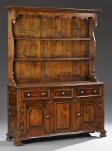English Carved Oak Welsh Cupboard, late 19th c., with an ogee crown over a scalloped skirt above two plate shelves, on a base with t...