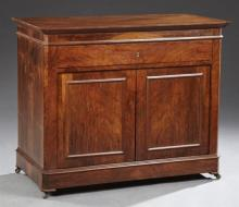 French Louis Philippe Style Carved Mahogany Sideboard, 19th c., the slanted edge top over a frieze drawer above double cupboard door...