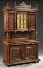 French Henri II Style Carved Walnut Buffet a Deux Corps, 19th c., the arched spindled crest over a stepped crown above a central arc...