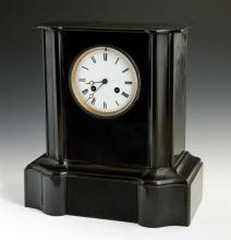 French Black Marble Mantel Clock, c. 1870, the shaped rectangular case with an enamel dial clock, time and strike, with Roman numera...