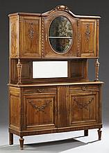 Louis XVI Style Carved Walnut Buffet a Deux Corps, c. 1900, the stepped arched top over an oval beveled glazed cupboard door flanked...