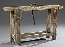 French Carved Elm Cabinet Maker's Workbench, 19th c., one side with a vise, the top with a clamp, on block legs joined by a bottom g...