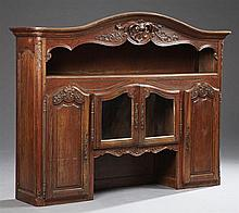 French Carved Oak Buffet Top, early 20th c., the stepped arched crest over open storage, above two central arched glazed doors over...