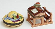 Two Hand-Painted Limoges Porcelain Pill Boxes, 20th c., of straw hat and school desk form, Desk- H.- 2 1/4 in., W.- 2 in., D.- 2 5/8...