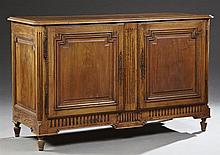 French Louis XVI Style Carved Oak Sideboard, late 19th c., the stepped canted corner top over double fielded panel cupboard doors wi...