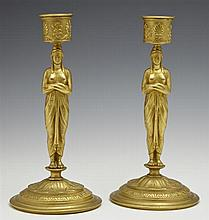 Pair of French Empire Style Gilt Bronze Candlesticks, 20th c., with relief decorated candle cups on classically draped female figure..