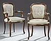 Pair of Louis XV Style Carved Walnut Fauteuils, 20th c., with a shield form back, the central carved flower crest within reeded edge...