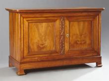 French Louis Philippe Carved Walnut Sideboard, 19th c., the rounded corner top over two cupboard doors centered by a carved stile, o...
