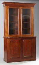 English William IV Carved Mahogany Bookcase Cupboard, 19th c., the cavetto carved frieze above two arched glazed cupboard doors, on...