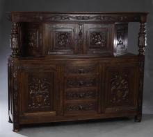 French Jacobean Style Carved Walnut Court Cupboard, early 20th c., the stepped cornice above two portrait carved cupboard doors flan...