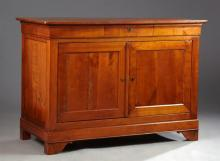 French Louis Philippe Carved Cherry Sideboard, mid 19th c., the rectangular rounded corner top over a cavetto frieze with a center d...