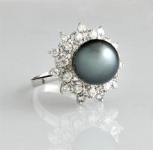 Lady's 14K White Gold Dinner Ring, with a 12 mm black Tahitian pearl, atop a pierced border of round diamonds separated by an outer...