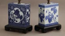 Pair of Chinese Porcelain Pillows, late 19th c., with blue and white decoration of Foo dogs, flowers and bats, now mounted on eboniz...