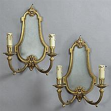Pair of Louis XVI Style Bronze Two Light Sconces, 20th c., with shaped mirror back plates issuing the scrolled leaf relief decorated...
