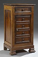 Louis Philippe Carved Walnut Nightstand, c. 1850, with a frieze drawer over a cupboard door with four faux drawers, on a plinth base...