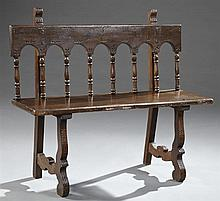 Spanish Carved Poplar Bench, c. 1850, with an arched spindled back, to a single board seat, on spoon carved trestle legs, H.- 37 3/4...