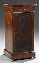 Louis Philippe Carved Mahogany Nightstand, c. 1850, the rounded corner top over a frieze drawer above a cupboard door, on a sloping...