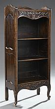 French Provincial Louis XV Style Carved Oak Open Bookshelf, c. 1900, the serpentine three-quarter galleried top over a carved flower...