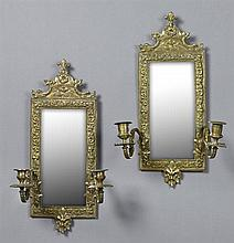 Pair of French Brass Two Light Sconces, 20th c., the arched tops over beveled mirrors, flanked by relief Indian masques issuing scro...