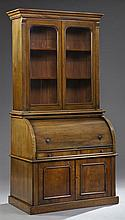 English Victorian Carved Walnut Cylinder Secretary Bookcase, late 19th c., the stepped ogee crown over double glazed doors, above a...