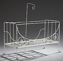 French Victorian Wrought Iron Folding Baby's Bed, 19th c., with a scrolling foliate decorated front rail and fabric crook, on caster..