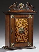 English Brass Mounted Mahogany Hanging Smoker's Cabinet, c. 1910, the broken arch crest with a central relief grotesque mask over a...