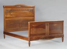 French Louis XVI Style Carved Walnut Double Bed, early 20th c., the arched leaf carved crest over an arched flower carved headboard,...