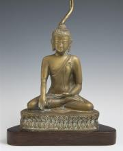 Oriental Gilt Bronze Seated Buddha Figure, early 20th c., the figure on a relief dais, now mounted on a triangular rosewood base as...