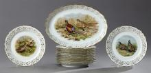 Thirteen Piece Porcelain Game Set, 20th c., consisting of twelve plates and a platter, each with gilt rims and gilt tracery borders...