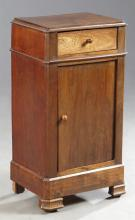 French Louis Philippe Carved Walnut Nightstand, 19th c., the canted corner top over a frieze drawer, above a cupboard door flanked b...