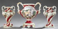 Three Piece Capodimonte Garniture Set, 20th c., consisting of a large baluster handled urn and a pair of smaller urns, each with rel...