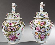 Pair of Meissen Style Carved Baluster Jars. 19th c., the lids with putti surmounts, with hand painted floral and butterfly decoratio...