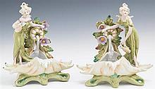 Pair of German Polychromed Bisque Figural Vases, 19th c., of shell form, depicting women at a fountain, H.- 8 5/8 in., W.- 8 in., D....