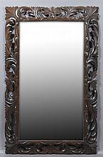 French Carved Oak Cushion Mirror, c. 1900, the pierced deep relief frame with scrolling leaves, around a wide beveled plate, H.- 60...