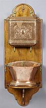 Large French Provincial Copper Lavabo, early 20th c., with repousse armorial decoration, on a carved oak back plate, H.- 46 in., W.-...