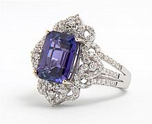 Lady's 18K White Gold Dinner Ring, with a 5.11 carat emerald cut tanzanite atop a pierced heart and loop shaped frame of pave diamon..