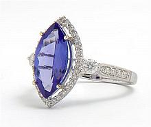 Lady's 14K White Gold Dinner Ring, with a 3.06 carat marquise tanzanite atop a border of pave diamonds, the sides of the band mounte..