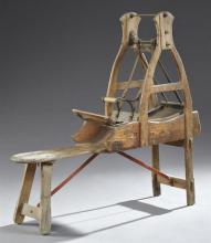 French Provincial Carved Pine and Iron Wool Carder, 19th c., on trestle legs joined by iron stretchers, H.- 44 in., W.- 46 in., D.-...