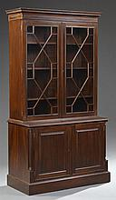 Georgian Style Carved Mahogany Bookcase, 20th c., the dentillated crown over double astragal glazed doors, on a base with double cup...