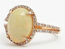 Lady's 14K Rose Gold Dinner Ring, with a 2.3 carat oval cabochon opal atop a border of pave diamonds, the split sides of the band al..