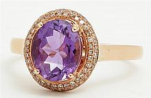 14K Rose Gold Lady's Dinner Ring, with an oval 1.6 carat amethyst atop a double concentric border of pave diamonds, total diamond we..