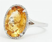 Lady's 14K White Gold Dinner Ring, with an oval 5.09 carat citrine atop a border of pave diamonds, on a split band, total diamond we..