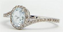 Lady's 14K White Gold Dinner Ring, with a central oval .68 carat aquamarine, atop a pave diamond mounted border, the sides of the by..