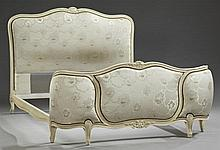 Louis XV Style Carved Beech Bed, 20th c., the arched headboard with a central floral carving over a floral upholstered panel, the sl...