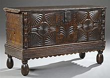 Spanish Carved Oak Coffer, 19th c., the two plank top above a leaf carved front, over a reeded scalloped skirt, on turned bun feet,...