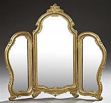 Louis XV Style Carved Giltwood Folding Triptych Dressing Mirror, early 20th c., the arched top with a leaf surmount, on a scrolled f...