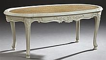 Louis XV Style Oval Cane Top Coffee Table, c. 1920, the inset cane top within a serpentine stepped edge, on flower carved cabriole l...